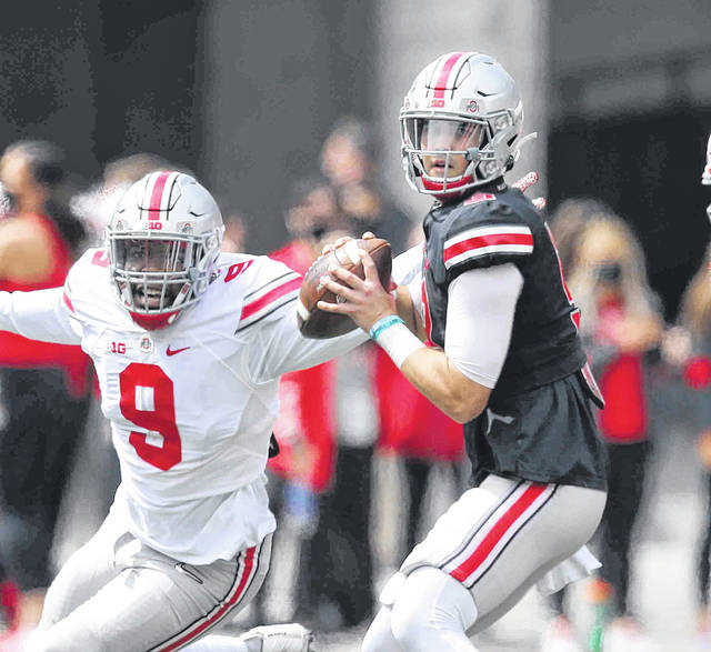 Jack Miller looks to make throw as Zach Harrison (9) closes in during Saturday's Ohio State spring game in Columbus.