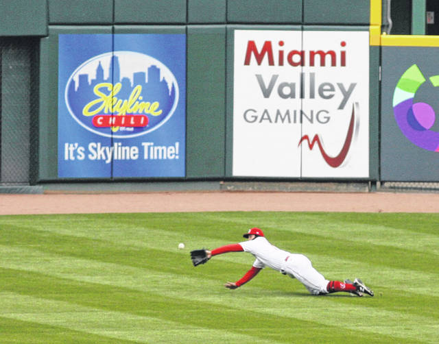 The Reds' Nick Senzel makes a diving catch during Thursday's opener in Cincinnati.