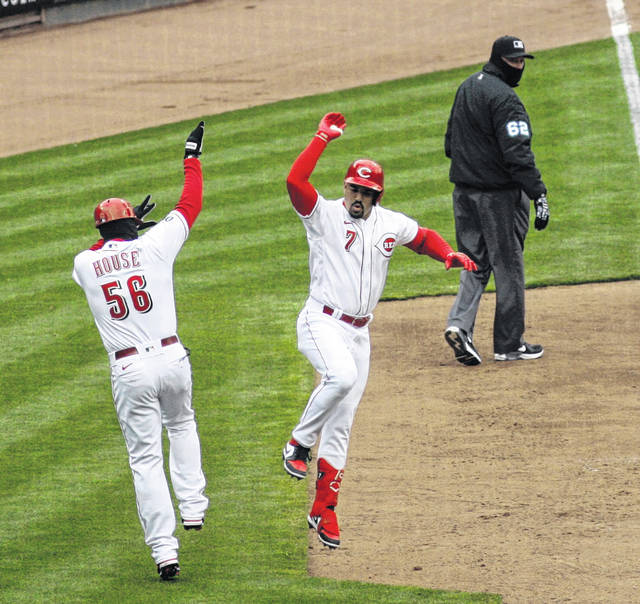The Reds' ugenio Suarez celebrates his first home run of the season with third base coach J.R. House during Thursday's opener in Cincinnati.