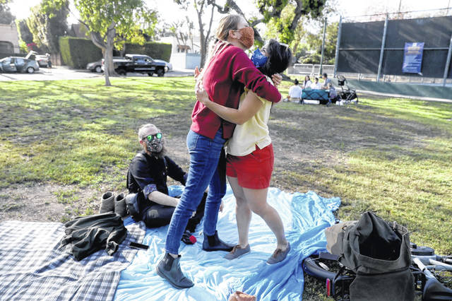 Jessica Holzer, 35, of West Hollywood, hugs friend Madeline Brozen, 35, of Los Angeles, for the first time since the COVID-19 pandemic, at Plummer Park on April 11 in Los Angeles, CA. Brandon Carpenter, sitting left, is Holzer's fiance. People are looking forward to hugging family and friends once they have their COVID-19 vaccine.
