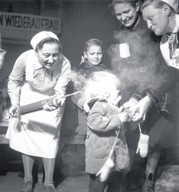 October 1945: A child crying as she is sprayed with DDT delousing powder at Nikolsburger Platz School in Wilmsdorf, Germany.