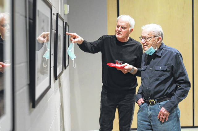 "John Klassen, of Wadsworth (left), and his father, Paul Klassen, of Bluffton, enjoy the new exhibit at the Allen County Museum, ""Richard Cook: Rail Images of a Past Era."" Amanda Wilson -The Lima News"