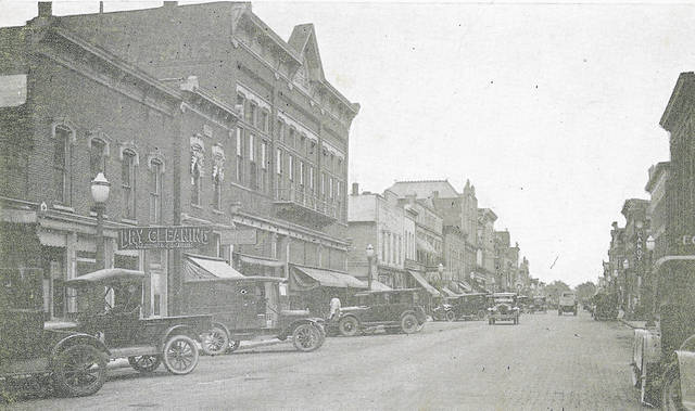 Old-style vehicles line the Wapakoneta Commercial Historic District, which received its marker for the National Register of Historic Places on Tuesday. A photo postcard shows Auglaize Street in Wapakoneta.