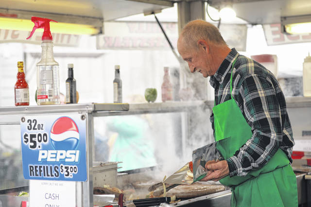 Roger Boyer, of Boyer Concessions, prepares a sandwich at the Cridersville Spring Food Truck Festival at the Cridersville Fire Department on Saturday afternoon.