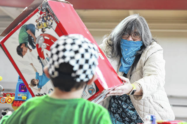 Four-year-old Carson Long, of Elida, buys a racetrack from Sue Kistler, of Cloverdale, during the Mom2Mom sale held at the Lima YMCA on Saturday morning.