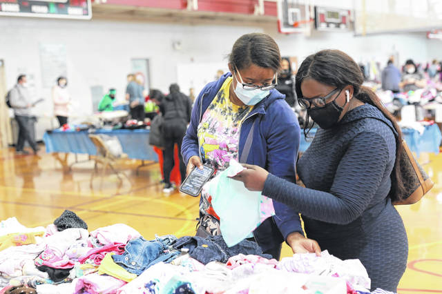 Aria Grant (left) and Sophia Hall, of Lima, rummage through baby clothes during the Mom2Mom sale held at the Lima YMCA on Saturday morning.