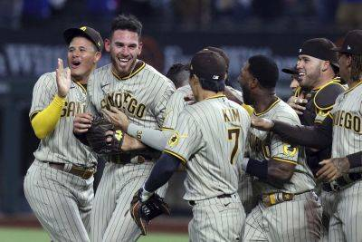 San Diego Padres starting pitcher Joe Musgrove, second from left, is mobbed by teammates Friday night after pitching a no-hitter against the Texas Rangers in Arlington, Texas. (AP photo)