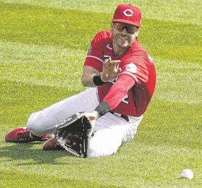 The Reds' Tyler Naquin is unable to catch a ball hit by Arizona's Josh Rojas during the 10th inning of Thursday's game in Cincinnati.