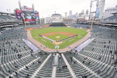 Baseball fans watch the opening ceremony before Thursday's Cleveland at Detroit game. The Tigers are allowing Comerica Park to be filled to about 20% capacity due to the COVID-19 pandemic.