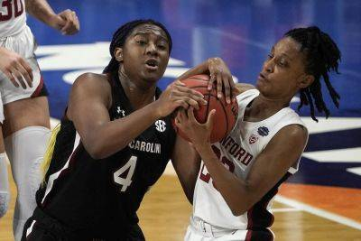 South Carolina's Aliyah Boston (4) fights for possession of the ball with Stanford's Kiana Williams during a Friday Final Four game at the Alamodome in San Antonio. (AP photo)