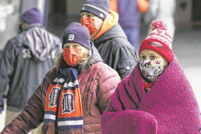 Fans wear masks and cold weather gear for Thursday's Cleveland at Detroit game. The temperature at game time was 32 degrees.