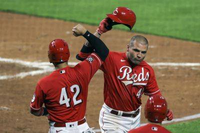 The Reds' Eugenio Suarez, left, celebrates with Joey Votto after Votto's third inning home run against the Cleveland Indians in Cincinnati. (AP photo)
