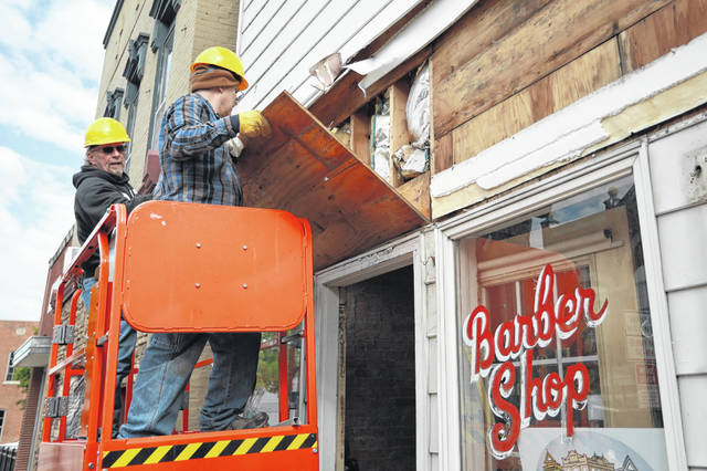 Louie Erb (left) and Everet Lacy pull down siding to reveal antique glass on Friday morning. Downtown Wapakoneta Partnership held a reveal at 122 West Auglaize Street after receiving a grant to remove the non-historic siding covering the 19th-century commercial building. The grant was made possible through the Pipeline Initiative Program administered by the Ohio Historic Preservation Office and the Ohio Development Services Agency.
