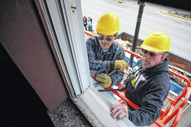 Louie Erb (right) and Everet Lacy remove an awning on Friday morning. Downtown Wapakoneta Partnership held a reveal at 122 West Auglaize Street after receiving a grant to remove the non-historic siding covering the 19th-century commercial building. The grant was made possible through the Pipeline Initiative Program administered by the Ohio Historic Preservation Office and the Ohio Development Services Agency.