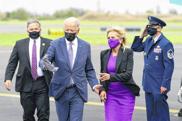President Joe Biden and first lady Jill Biden walk to a motorcade vehicle after stepping off Air Force One at Philadelphia International Airport in Philadelphia on Friday.