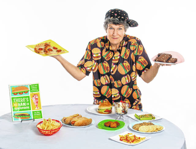 """Kim Zachman poses with her book and plates of food on Oct. 5, 2020, in Roswell, Ga. Zachman's book for young readers, """"There's No Ham in Hamburgers,"""" offers kids ages 8 to 12 a fun-filled journey through the history of some of their favorite foods."""