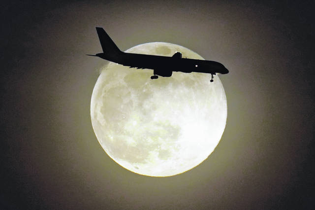 A jet is silhouetted by the rising moon April 26 as it approaches Louisville International Airport in Louisville, Ky. Air travel continues to recover from the pandemic, although it's still not close to normal. The Transportation Security Administration said that nearly 1.67 million people were screened at U.S. airport checkpoints on May 2.
