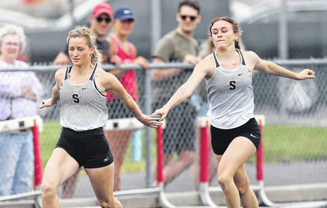 Spencerville's Gillian Goecke (right) hands the baton off to Ariana McMichael during the 800 relay at Saturday's Spencerville Division III district. See more track and field photos at LimaScores.com.