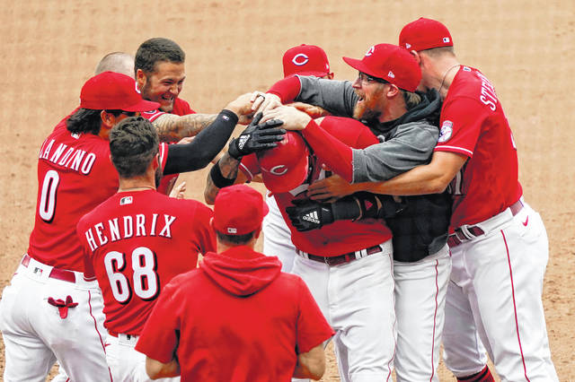 Cincinnati Reds outfielder Nick Castellanos (2) celebrates with teammates after hitting a walk-off RBI single in the 10th inning of a 13-12 win over the Chicago Cubs in Cincinnati on Sunday.