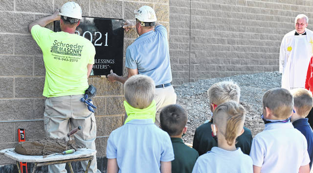 Evan Schroeder, left, and Tim Schroeder, middle, of Schroeder Masonry, place the cornerstone into the brickwork for the addition at SS. Peter and Paul Catholic School in Ottawa on Friday.