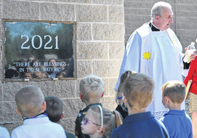 Father Scott Kramer, right, of SS. Peter and Paul Catholic Church in Ottawa, explains to pupils how floodwaters in 2007 like the river waters in the bottle helped bring about an addition on to the school. The parish placed a cornerstone on its new addition for kindergarten through third-grade classrooms Friday. See more photos from the school on LimaOhio.com.