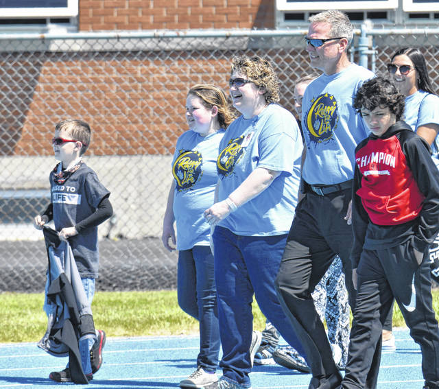 """Rich Dackin, superintendent of Bath Local Schools, joined students Lauren Cunningham, Dagan Hawkins and Mason Jackson and school district employee Mariah Ross — all cancer surivors — for a ceremonial """"Survivors Lap"""" around the school's track on Friday as part of the annual Relay for Life fundraiser to benefit the American Cancer Society."""
