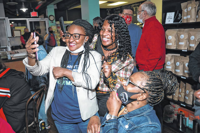 Sharetta Smith, left, shares a phone with family and friends while awaiting Lima mayoral primary results Tuesday night at The Meeting Place on Market. Smith finished first in the four-way nonpartisan primary election and advances to November's general election.