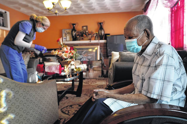 Edouard Joseph, 91, right, clasps his hands as geriatrician Megan Young, left, prepares to give him a COVID-19 vaccination at his home in Boston. A majority of Americans agree that government should help people fulfill a widely held aspiration to age in their own homes.