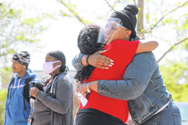 Taylor Pennington, right, hugs Joeann Brown at the Rally 4 Change in the town square on Saturday afternoon.