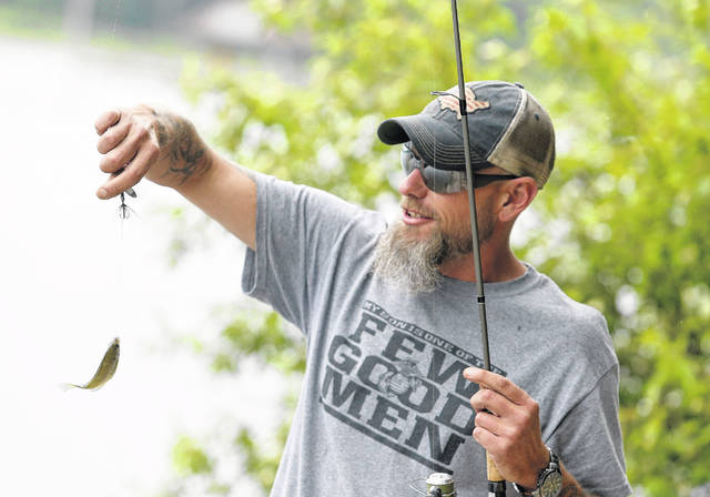 Tyler Moncrief of Canton Township catches a bluegill Friday at Sippo Lake in Perry Township.