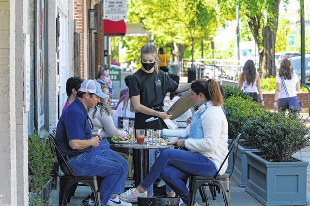 Patrons are assisted April 16 while dining along a sidewalk on Franklin Street in Chapel Hill, N.C. As consumers increasingly venture away from home, demand has begun to shift away from manufactured goods and toward services, from airline fares to restaurant meals, triggering inflation in those areas.