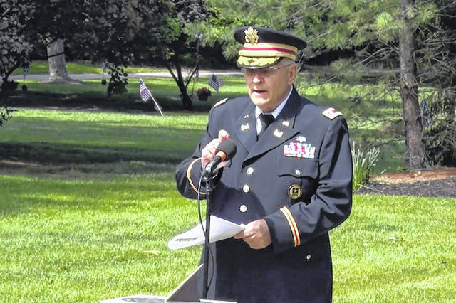 Retired Army Lt. Col. Barnard Kemter taps the microphone after organizers turned off the audio during his speech at a Memorial Day ceremony May 31 in Hudson, Ohio. Organizers of the ceremony turned off Kemter's microphone when he began talking about how freed Black slaves had honored fallen soldiers soon after the Civil War.