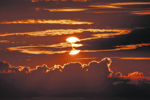 A partial solar eclipse rises behind clouds Thursday in Arbutus, Md.