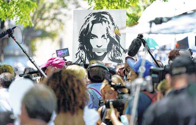 A portrait of Britney Spears looms over supporters and media members outside a court hearing June 23 concerning the pop singer's conservatorship at the Stanley Mosk Courthouse in Los Angeles.