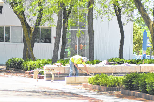 A man works on the exterior of Rhodes State's Borra Center for Health Science Education & Innovation on Monday afternoon.