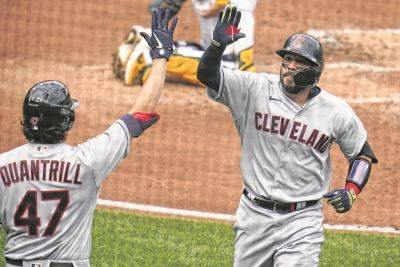 Cleveland's Rene Rivera is congratulated by Cal Quantrill (47) as he returns to the dugout after hitting a home run during Saturday's game in Pittsburgh.