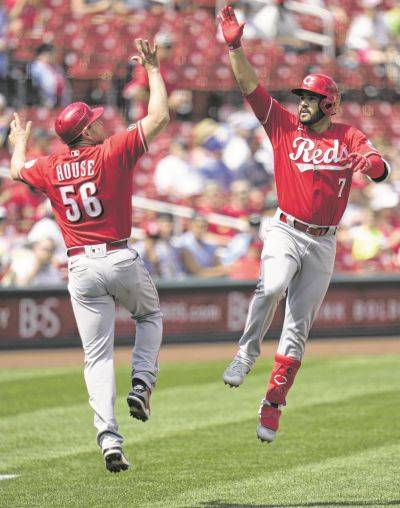 Cincinnati's Eugenio Suarez (7) celebrates his home run with third base coach J.R. House during Saturday's game against the Cardinals in St. Louis.
