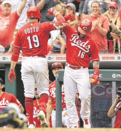 The Reds' Joey Votto (19) celebrates hitting a solo home run with Tucker Barnhart during Thursday's game against Milwaukee in Cincinnati.