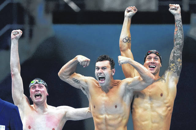 United States men's 4x100m freestyle relay team Bowen Becker, Blake Pieroni, and Caeleb Dressel celebrate after winning the gold medal at the 2020 Summer Olympics, Monday in Tokyo, Japan.