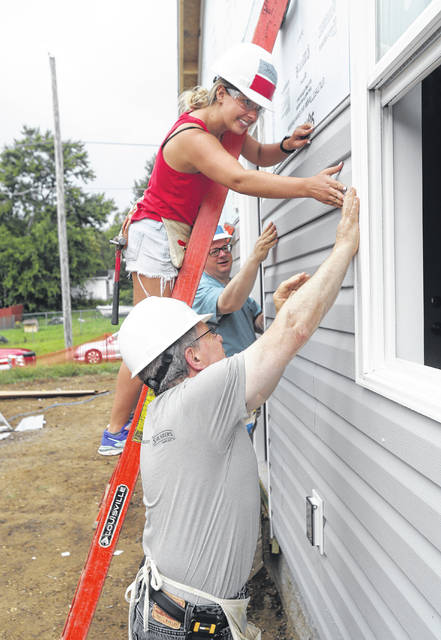 Jenna Tenenbaum works to install a piece of siding with help from Temple Israel Rabbi David Komerofsky, rear, and Mark Atleson. The group is volunteering as a part of Faith Build, Habitat for Humanity's interfaith building project in Canton.