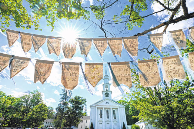 Flags with names of people who have died from COVID-19 are displayed outside the First Congressional Church on June 17, 2021, in Holliston, Mass.