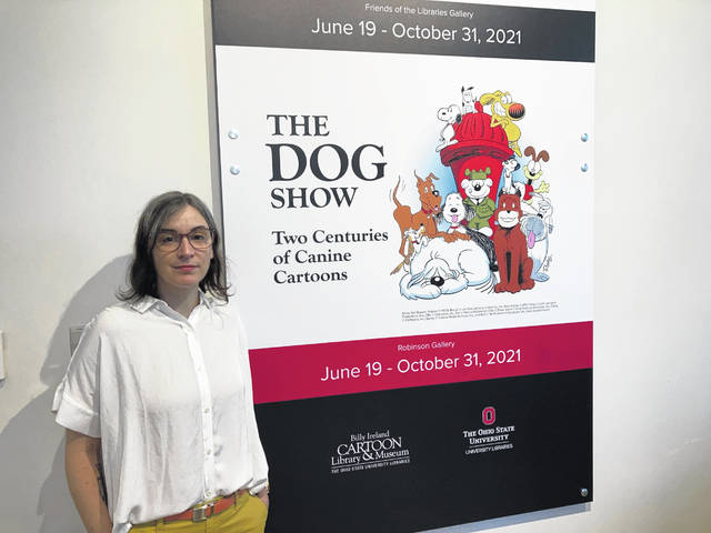 """Anne Drozd, museum coordinator at Ohio State University's Billy Ireland Cartoon Library Museum, stands at the entrance to the library's new exhibit, """"The Dog Show,"""" on June 24 in Columbus, Ohio."""