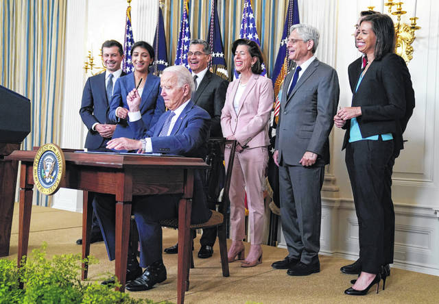 President Joe Biden hands out a pen Friday after signing an executive order aimed at promoting competition in the economy, in the State Dining Room of the White House in Washington. Standing from left, Transportation Secretary Pete Buttigieg, Lina Khan, Chair of the Federal Trade Commission, Health and Human Services Secretary Xavier Becerra, Commerce Secretary Gina Raimondo, Attorney General Merrick Garland, National Economic Council director Brian Deese, obscured, and Jessica Rosenworcel, Acting Chairwoman of the Federal Communications Commission.