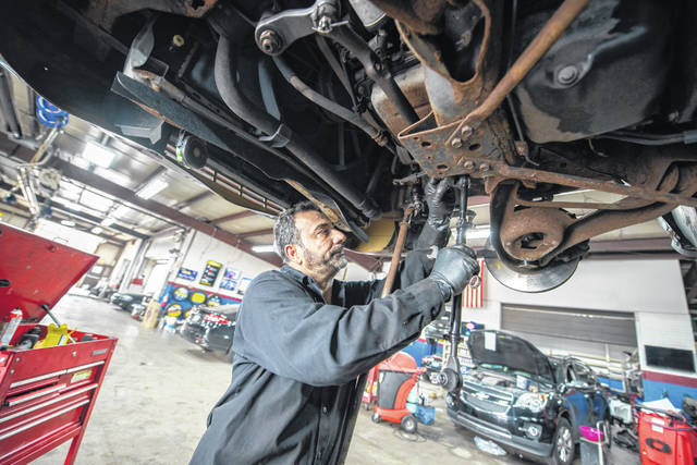 Mechanic Mazen Alsabbagh works on the suspension of a 2000 Mercury Grand Marquis on July 7 at Jay's Auto Repair, in Detroit, Michigan.