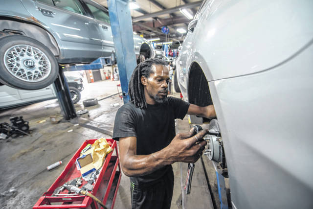 Mechanic A.J. Jenkins works on the brakes of a Ford Fusion on July 7 at Jay's Auto Repair, in Detroit, Michigan.