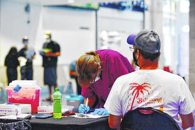 A nurse prepares paperwork with a patient during the Vaccinate at the Plate event at Tropicana Field on June 16, 2021, in St Petersburg, Florida.