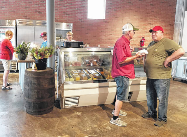 Farmhouse Market and Deli owner Mike Schroeder, far right, talks with a customer at their store in Columbus Grove.