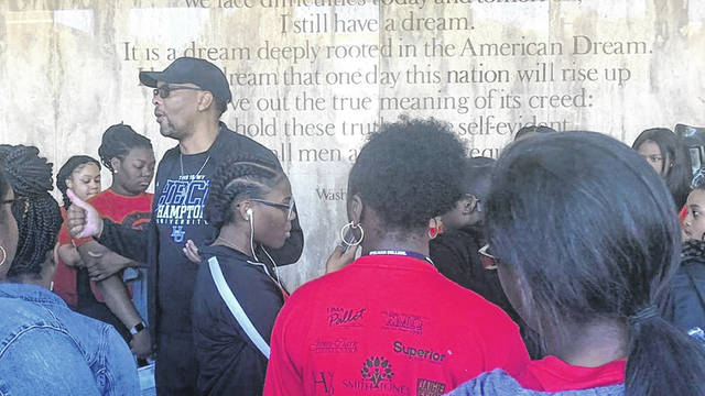 A tour guide speaks to the Lima Educational Field Trip group in 2019 alongside a quote from Martin Luther King Jr.