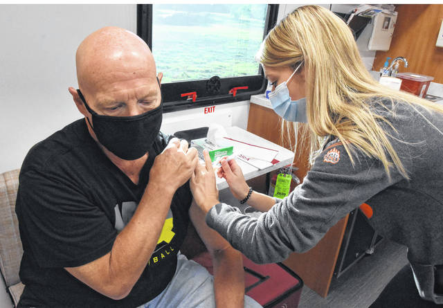 Todd Henkle of Lima, left, receives a flu vaccine by Ashlyn Corconnier, an ONU HealthWise student, during a Mobile Health Clinic held at Area Agency on Aging in Lima. The clinic offered flu vaccines, bone density scans and blood pressure checks. Licensed medical staff was on hand to oversee ONU HealthWise students.