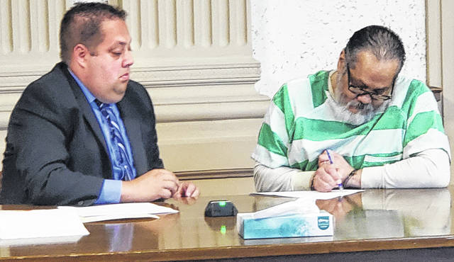 """Jesus Tapia Jr., right, signs a """"no contest"""" plea to a rape charge while his attorney, Barry Schroeder, watches Tuesday. Tapia faces 11 to 16 1/2 years in prison when he's sentenced Aug. 12."""